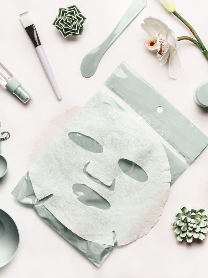 Gesichtsblattmasken- und -kosmetikwerkzeuge mit Orchidee blüht auf weißem Tischplattenhintergrund, Draufsicht stockbild