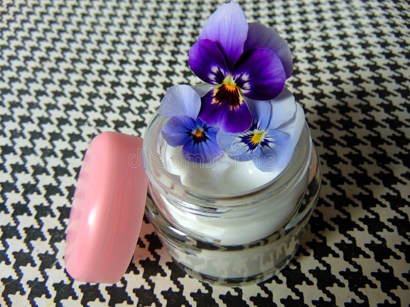 Gesichtscreme für gute Hautpflege mit purpurroten Blumen lizenzfreie stockfotografie