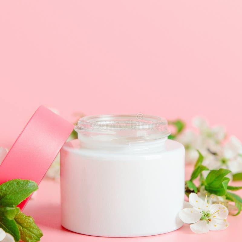 Gesichtscreme im weißen Glas und in der rosa Abdeckung auf einem rosa Hintergrund mit weißen Blumen Konzeptnaturkosmetik, organis stockbild