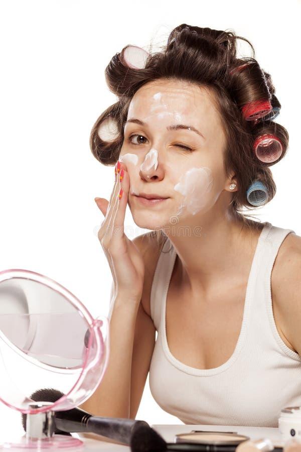 Gesichtscreme und Haarlockenwickler stockbild