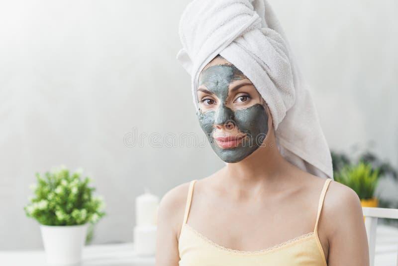Gesichtshautpflege Attraktive junge Frau eingewickelt im Bad-Tuch, Lehmschlammmaske anwendend, um gegenüberzustellen Nahaufnahmep stockfotografie