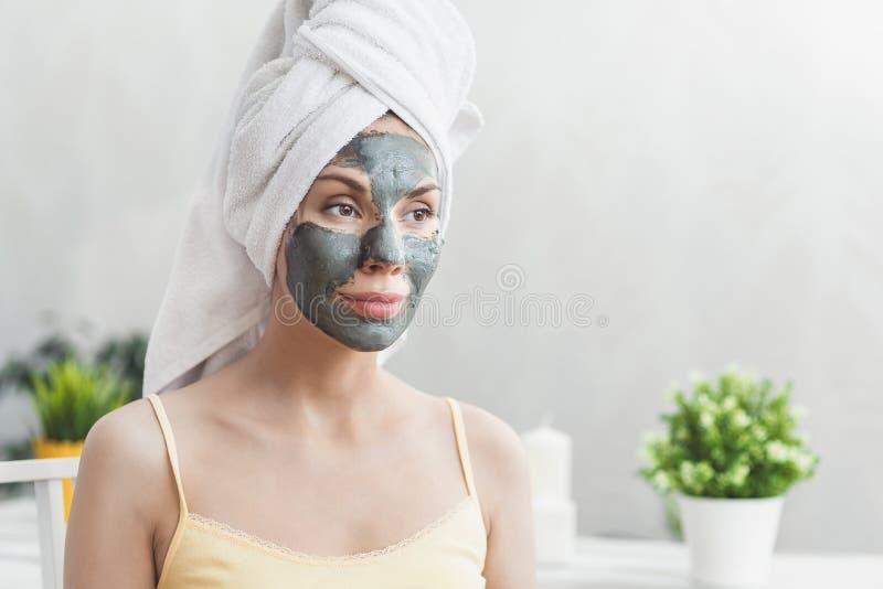 Gesichtshautpflege Attraktive junge Frau eingewickelt im Bad-Tuch, Lehmschlammmaske anwendend, um gegenüberzustellen Nahaufnahmep lizenzfreie stockfotos