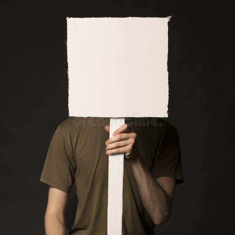 Gesichtslose Person, die ein leeres Zeichen hält stockfoto