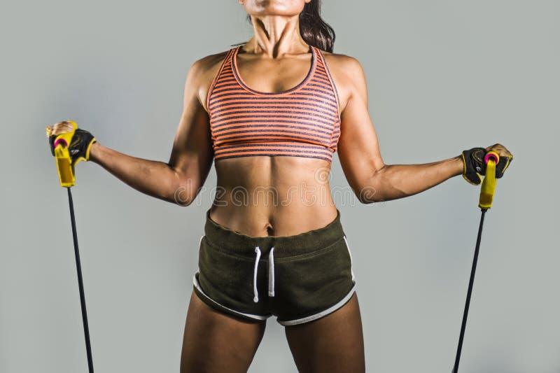 Gesichtsloses Porträt der Frau des Jungesitzes und des athletischen Sports, die schwer mit elastischem Widerstand arbeitet, versi lizenzfreies stockbild