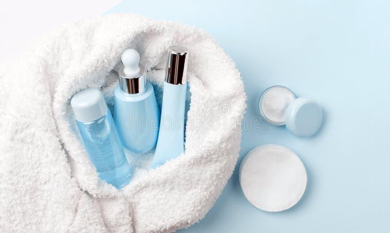 Gesichtspflegemittelstärkungsmittel oder Lotion, Serum, Creme, micellares Wasser, Baumwollauflagen bedeckt im Tuch auf Blau, Pulv lizenzfreies stockfoto