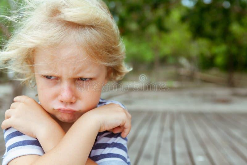 Gesichtsporträt des gestörten, unglücklichen kaukasischen Kindes mit den gekreuzten Armen stockbild
