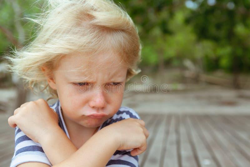 Gesichtsporträt des gestörten, unglücklichen kaukasischen Kindes mit den gekreuzten Armen lizenzfreies stockfoto