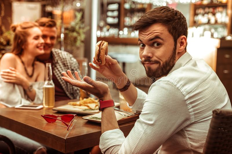 Gesichtsporträt von männlichen zuckenden Schultern während seine streichelnden Freunde stockbilder
