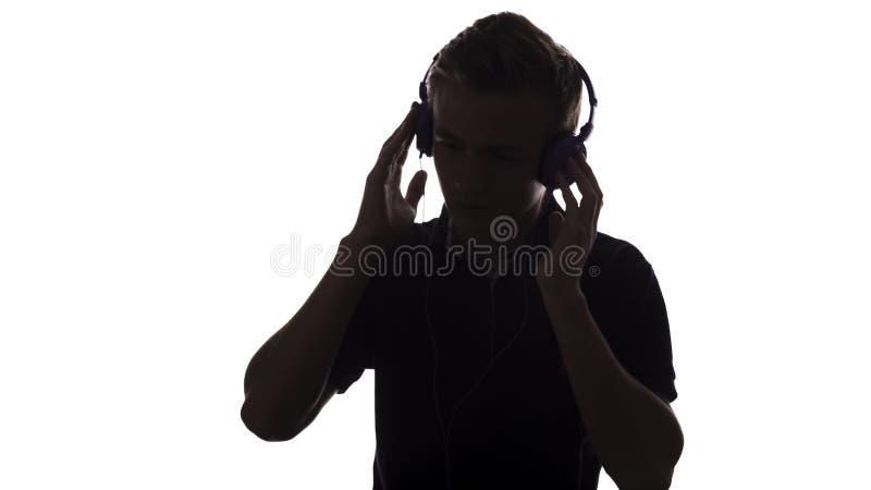 Gesichtsprofilschattenbild des Musikfreundjugendlichen hörend auf Lieblingslied in den Kopfhörern, hübscher junger Mann auf Weiß stockfotografie