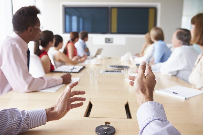 Gesichtspunkt geschossen von den Wirtschaftlern um Sitzungssaal-Tabelle stockbild