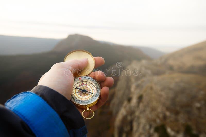 Gesichtspunktfoto des Forschermannes Richtung mit goldenem Kompass in seiner Hand mit Herbstgebirgshintergrund suchend lizenzfreie stockfotos