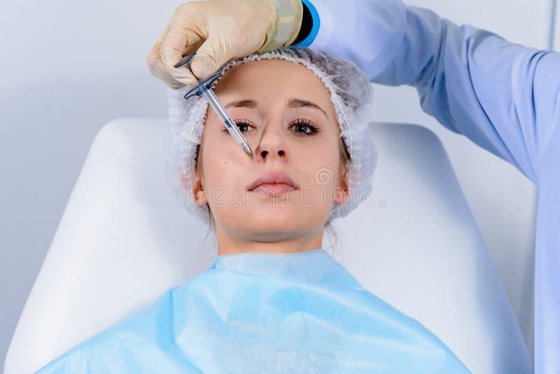 Gesichtsverjüngungsverfahren - Manndoktor spritzt Einspritzungen der Hyaluronsäure in Nasolabialfalten zur jungen Klientin ein stockbilder