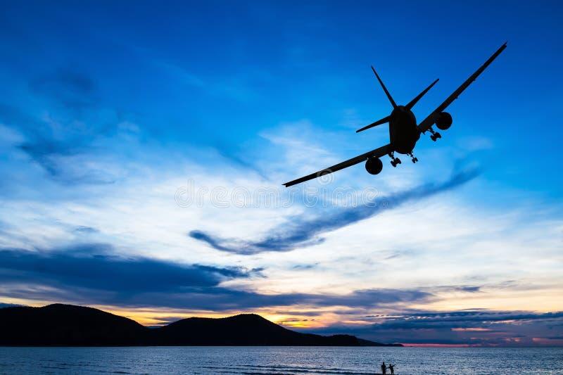 Gesilhouetteerd commercieel vliegtuig die bij zonsondergang vliegen stock afbeeldingen