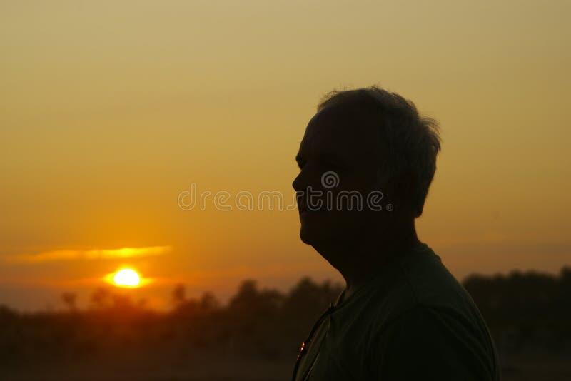 Gesilhouetteerde mens in de zonsondergang stock foto