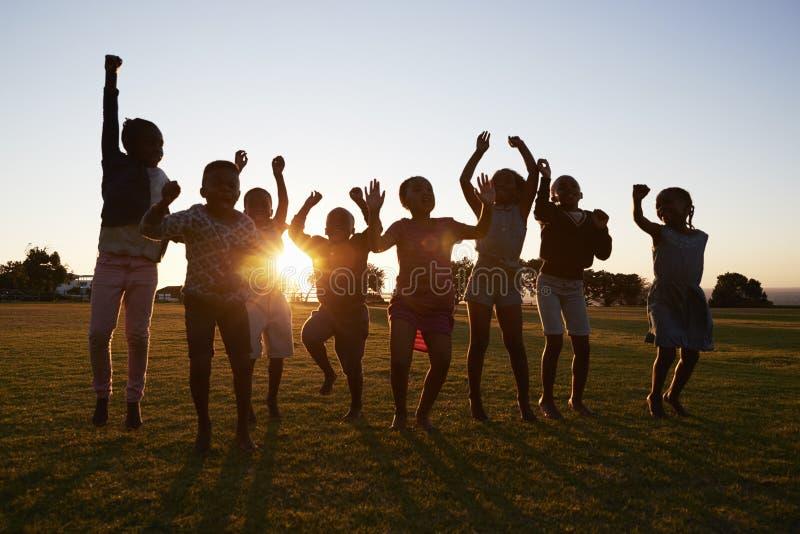 Gesilhouetteerde schooljonge geitjes die in openlucht bij zonsondergang springen stock afbeelding
