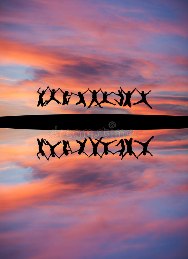 Gesilhouetteerde tienerjaren die handen houden en in zonsonderganghemel springen stock foto's