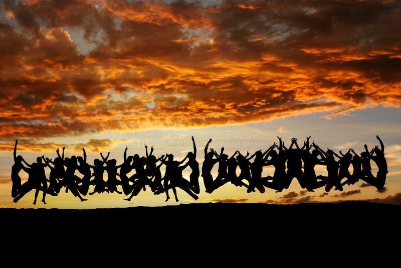 Gesilhouetteerde tienerjaren die in zonsondergang springen royalty-vrije stock fotografie