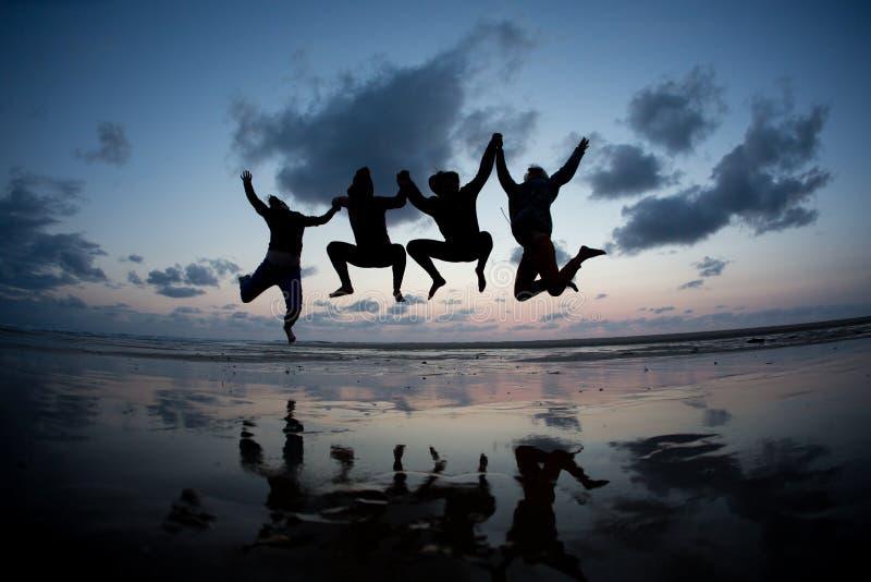Gesilhouetteerde vrienden die in zonsondergang bij strand springen royalty-vrije stock foto's