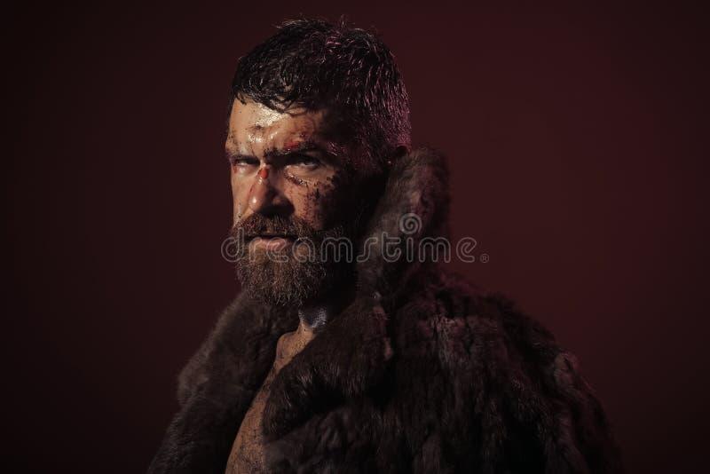 Geslagen Mens Mens met baard, snor op bloedig gezicht in bontjas stock foto