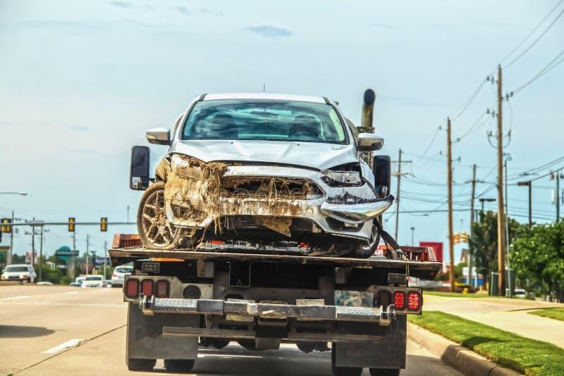 Gesloopte auto met modder en installatiemateriaal het plakken uit grill en van onder kap op flatbed vrachtwagen in stad - mogelij stock foto