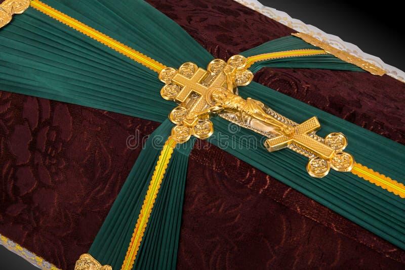 Gesloten die doodskist met bruine en groene die doek wordt behandeld met Kerk gouden kruis wordt verfraaid op grijze luxeachtergr stock afbeelding