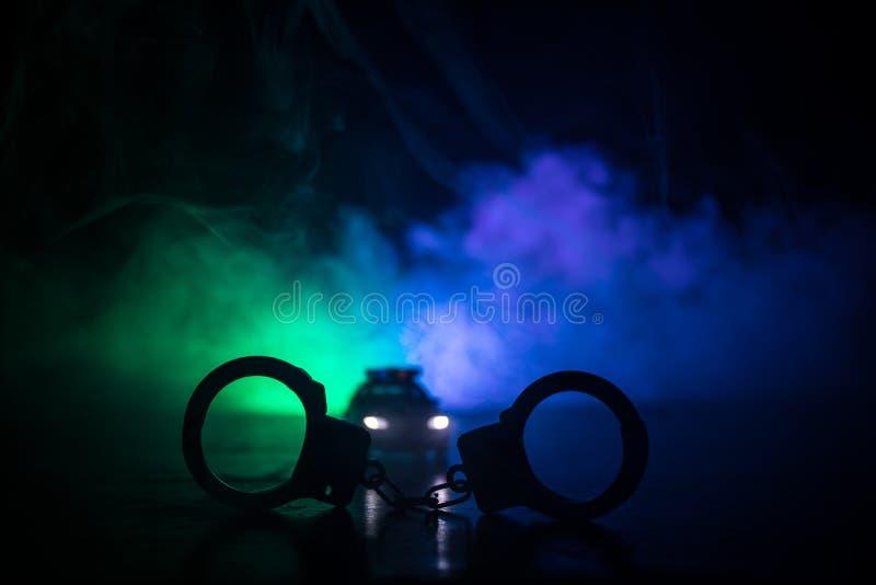 Gesloten handcuffs op de straatbestrating bij nacht met politiewagenlichten royalty-vrije stock afbeeldingen