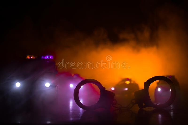 Gesloten handcuffs op de straatbestrating bij nacht met politiewagenlichten stock afbeelding