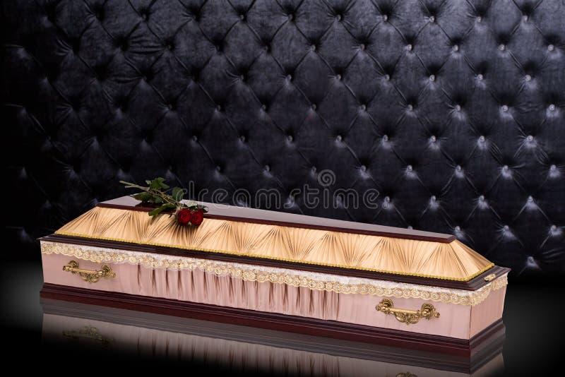 Gesloten houten beige doodskist met rode die rozen met doek worden behandeld op grijze luxeachtergrond wordt ge?soleerd kist met  stock illustratie