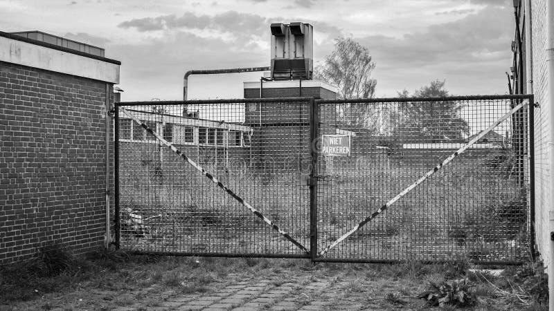 Gesloten ijzerpoort dichtbij een gesloten fabriek Almelo, Nederland royalty-vrije stock fotografie