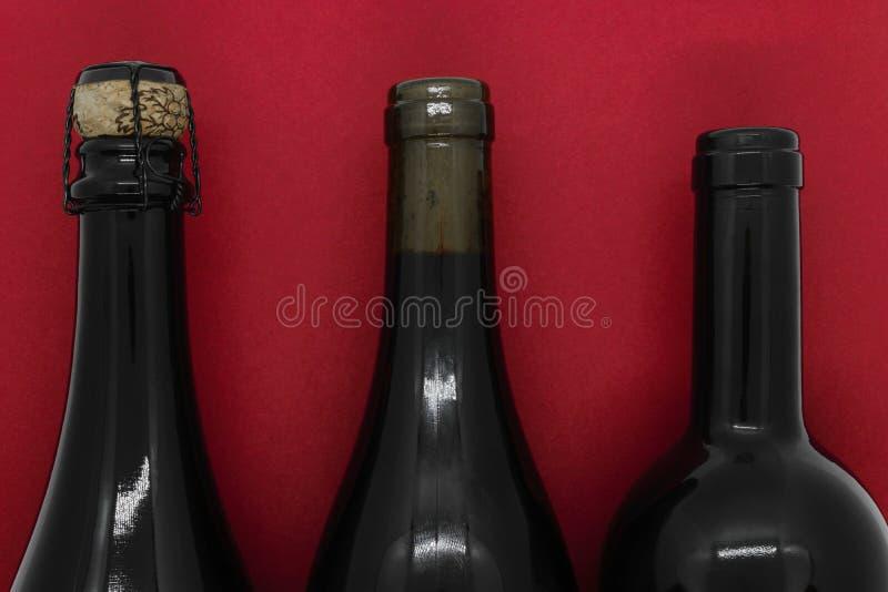 Gesloten met kurkt champagne en wijn zwarte flessen op rode achtergrond royalty-vrije stock foto's
