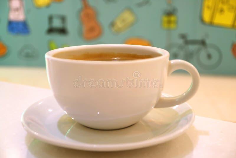 Gesloten omhoog hete koffie in een witte kop met vaag kleurrijk muurdocument op achtergrond stock foto's