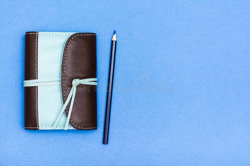 Gesloten organisator in een band van het twee kleurenleer en een potlood op een blauwe achtergrond Hoogste mening stock foto's