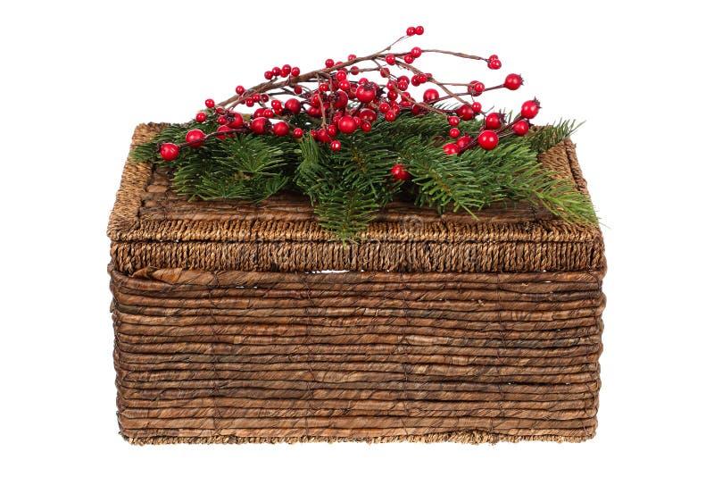 Gesloten rieten die picknickmand voor Kerstmis met pijnboomtakjes en van hulstbessen ornamenten wordt verfraaid op witte achtergr stock afbeelding