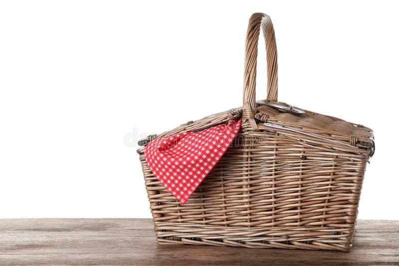 Gesloten rieten picknickmand met geruit tafelkleed op houten lijst royalty-vrije stock foto