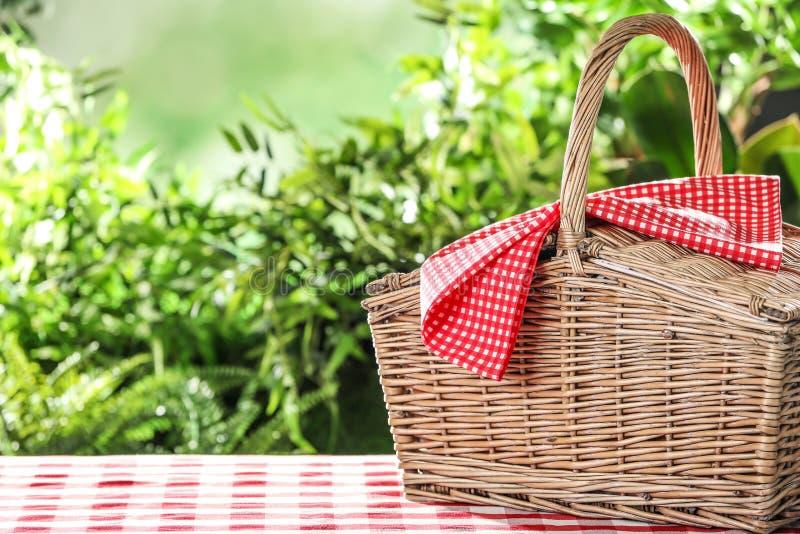 Gesloten rieten picknickmand op geruit tafelkleed tegen vage achtergrond royalty-vrije stock afbeelding