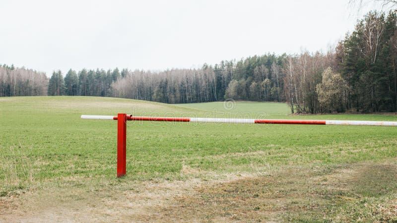 Gesloten rode en witte barrière bij bosingang stock fotografie