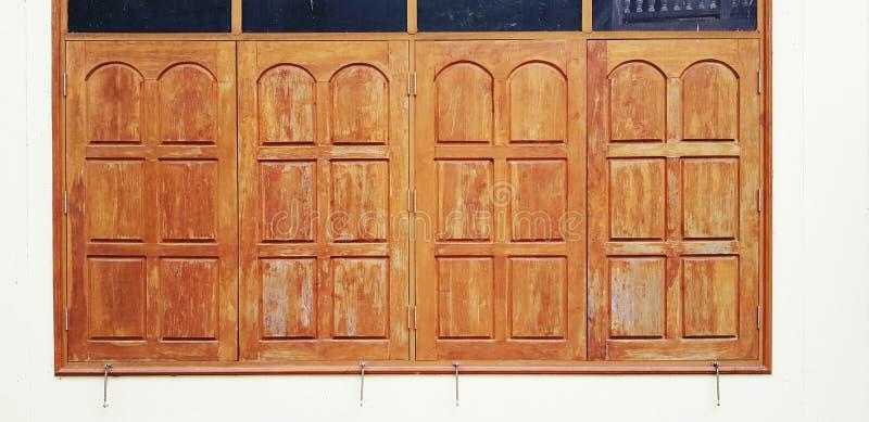 Gesloten uitstekend houten venster met zwart die glas op bovenkant op witte concrete muurachtergrond wordt geïsoleerd royalty-vrije stock fotografie
