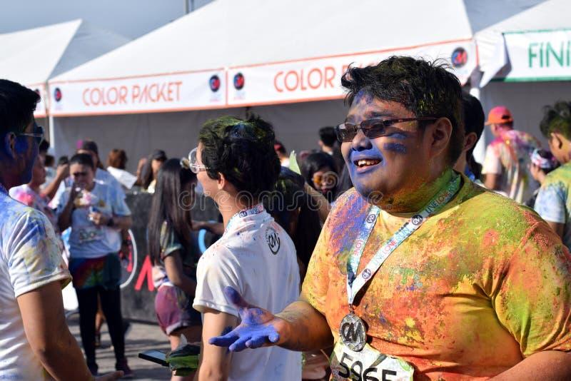 Gesmeerd met gekleurde kleurstoffen, schittert de jongeren die pret hebben bij de Kleur Manilla Looppas royalty-vrije stock foto