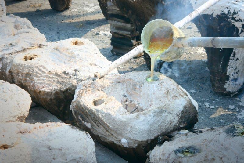 Gesmolten goud dat van een gieterijsmeltkroes wordt gegoten royalty-vrije stock afbeeldingen
