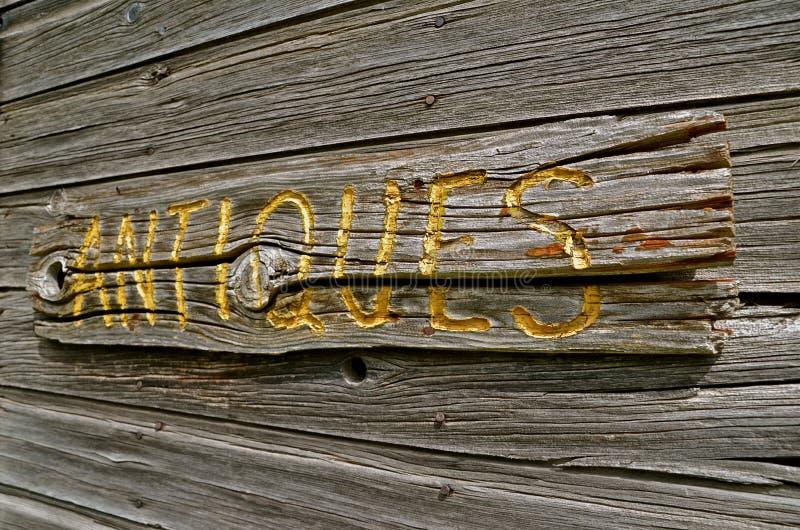Gesneden 'ANTIEK 'houten teken op doorstaan hout stock foto's