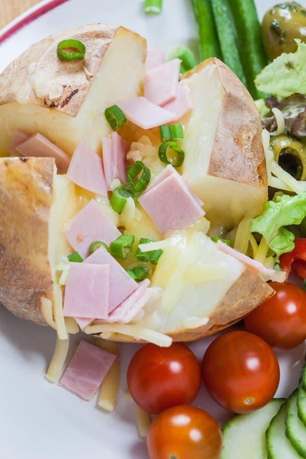 Gesneden aardappel in de schil met gesmolten kaas en boter royalty-vrije stock foto