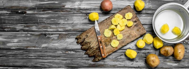 Gesneden aardappels op een scherpe Raad met een mes en gepelde aardappels in een steelpan royalty-vrije stock afbeelding