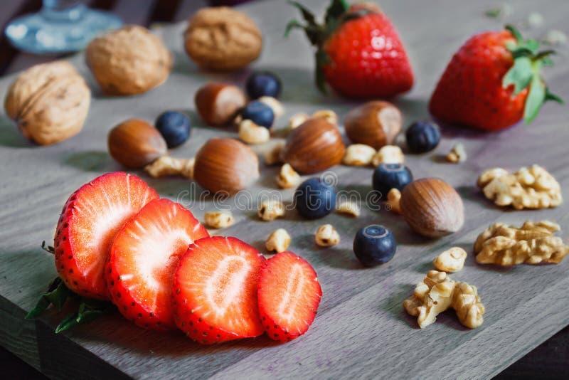 Gesneden aardbei met noten op een houten lijst stock foto