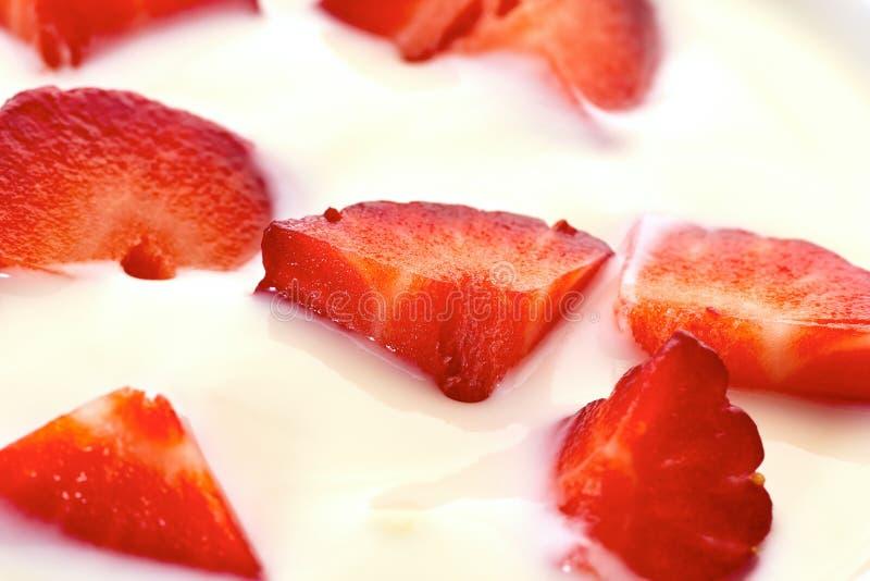 Gesneden aardbeien in yoghurt stock afbeeldingen