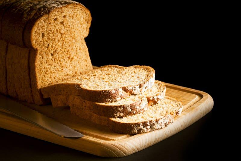 Gesneden bruin brood op houten hakbord stock afbeeldingen