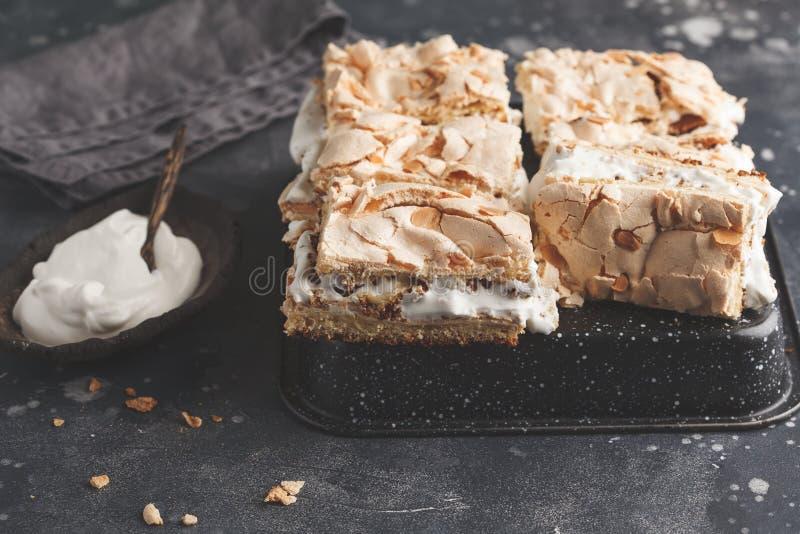 Gesneden cake met schuimgebakje en slagroom, donkere achtergrond royalty-vrije stock afbeelding