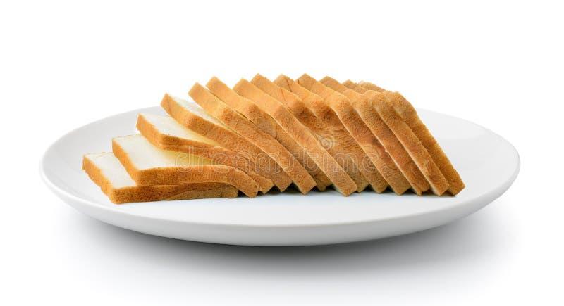 Gesneden die brood in een plaat op een witte achtergrond wordt geïsoleerd stock afbeeldingen