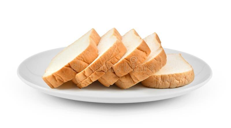 Gesneden die brood in plaat op witte achtergrond wordt geïsoleerd stock foto's