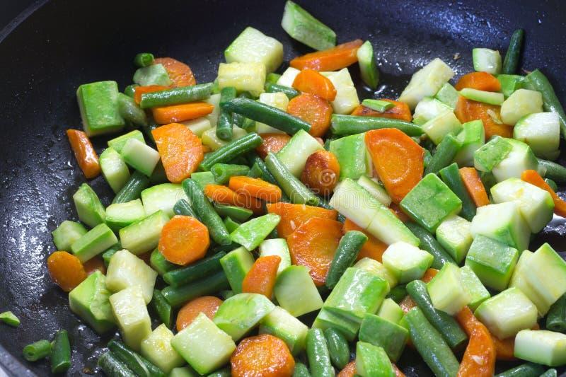Gesneden die groenten, in boter in een pan worden gebraden royalty-vrije stock afbeelding