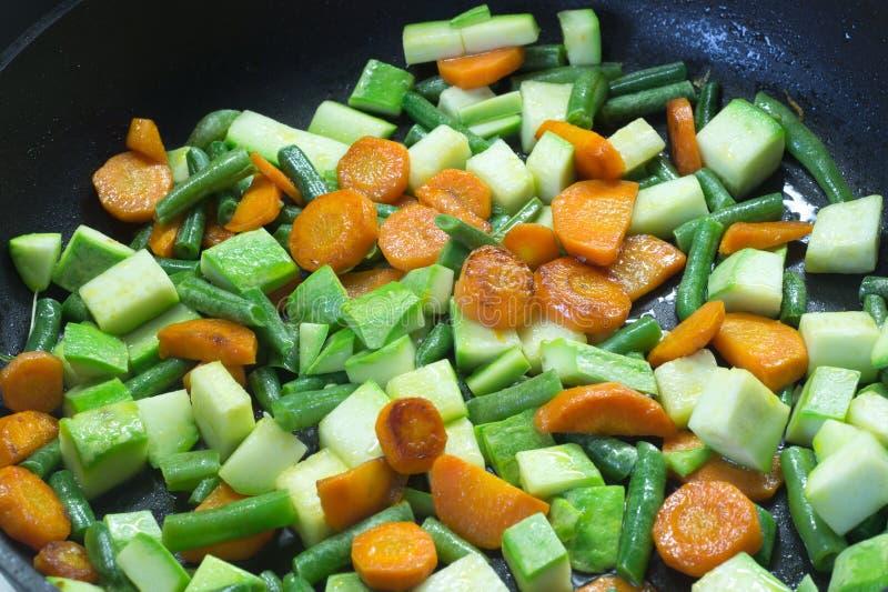 Gesneden die groenten, in boter in een pan worden gebraden stock fotografie